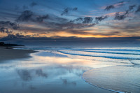 Sunrise seascape with cloud reflections on the beach