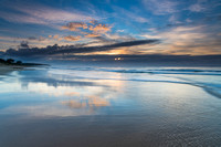 Sunrise Seascape with Clouds and Reflections on the Beach