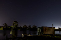 Dam, shed, trees and stars nightscape