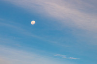 The Moon and White and Blue High Clouds in the Sky at Sunset